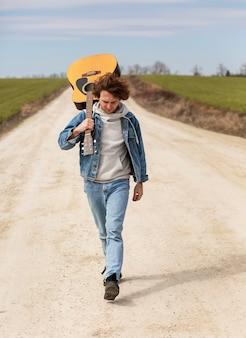 Hombre de tiro completo caminando con guitarra