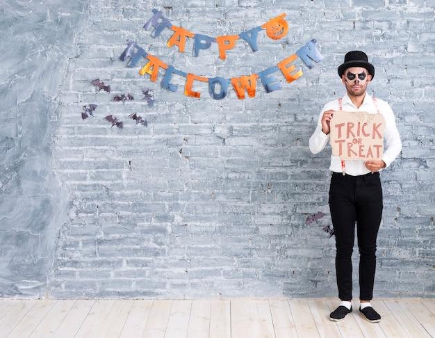 Hombre de tiro completo con cartel de truco o trato para halloween