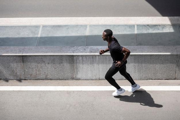 Hombre de tiro completo corriendo al aire libre