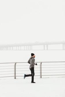 Hombre de tiro completo corriendo en la nieve