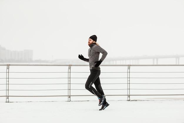 Hombre de tiro completo corriendo con nieve
