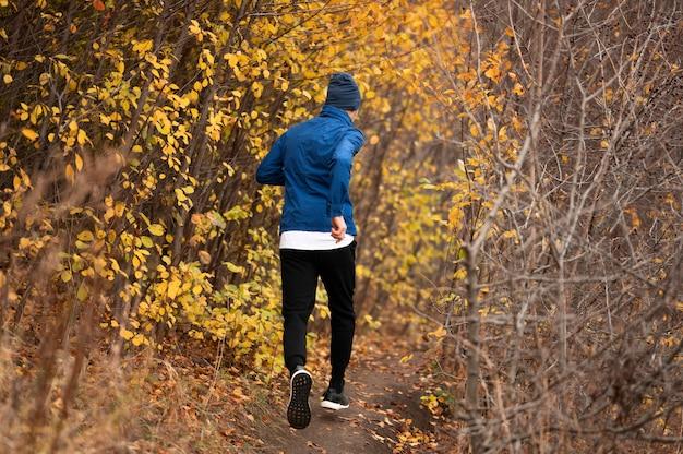 Hombre de tiro completo corriendo en sendero en el bosque