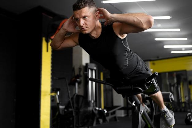 Hombre de tiro completo entrenando en el gimnasio
