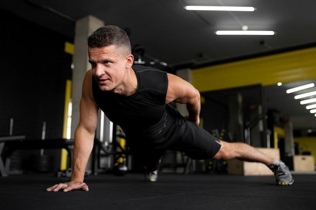 Hombre de tiro completo haciendo flexiones