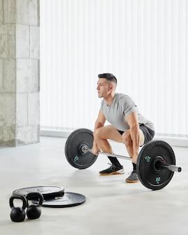 Hombre de tiro completo levantando pesas en interiores