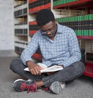 Hombre de tiro completo leyendo en el piso