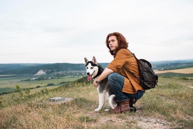 Hombre de tiro completo con perro al aire libre