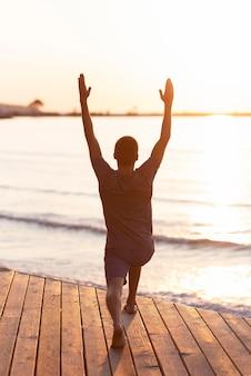 Hombre de tiro completo practicando yoga hacia el mar y el sol