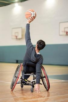 Hombre de tiro completo en silla de ruedas en la cancha de baloncesto