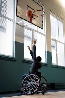 Hombre de tiro completo en silla de ruedas jugando baloncesto