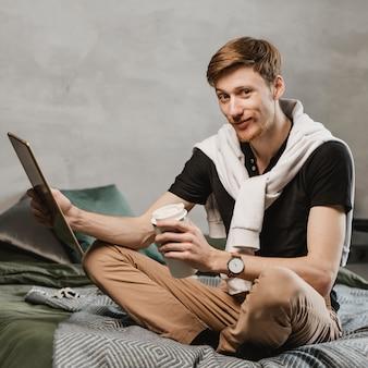Hombre de tiro completo con tableta y café