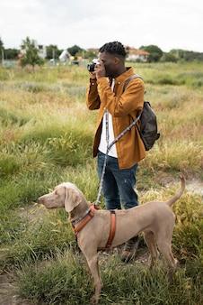 Hombre de tiro completo tomando fotos en la naturaleza