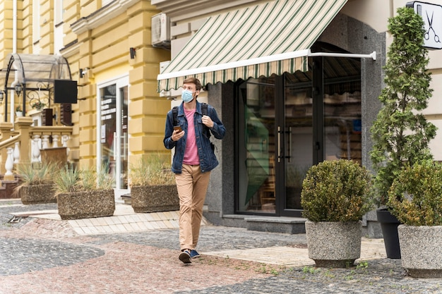 Hombre de tiro largo caminando afuera con una máscara médica en