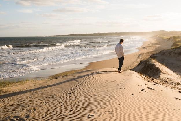 Hombre de tiro largo caminando en la playa