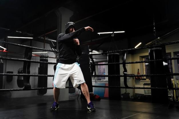 Hombre de tiro largo en entrenamiento de ropa deportiva en ring de boxeo