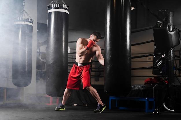 Hombre de tiro largo entrenando para la competencia de boxeo