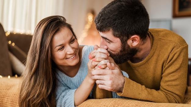 Hombre de tiro medio besando la mano de la mujer