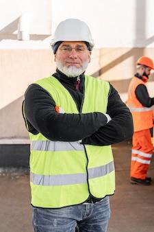 Hombre de tiro medio con casco en el trabajo
