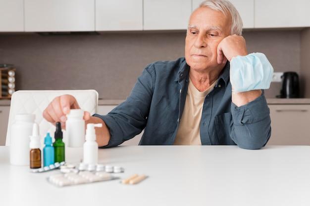 Hombre de tiro medio con contenedor de pastillas