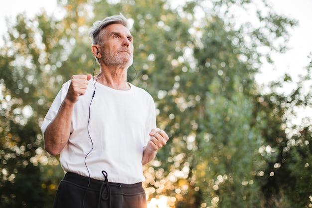 Hombre de tiro medio corriendo al aire libre
