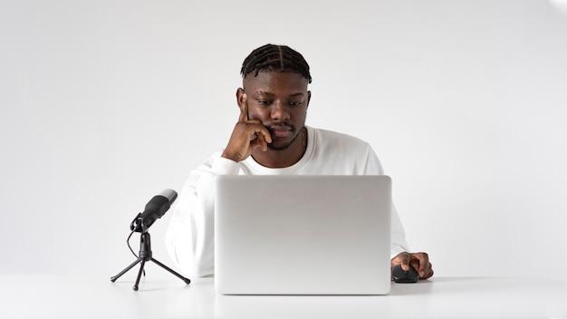 Hombre de tiro medio en el escritorio con micrófono