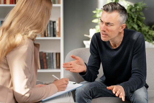 Hombre de tiro medio hablando con terapeuta de mujer