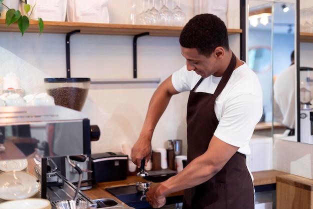 Hombre de tiro medio haciendo café