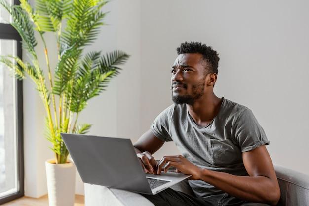 Hombre de tiro medio con laptop pensando