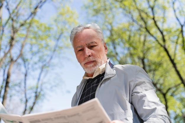 Hombre de tiro medio leyendo el periódico
