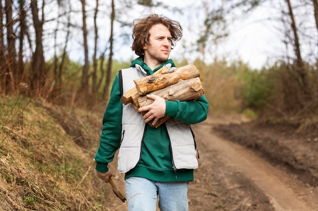 Hombre de tiro medio llevando madera
