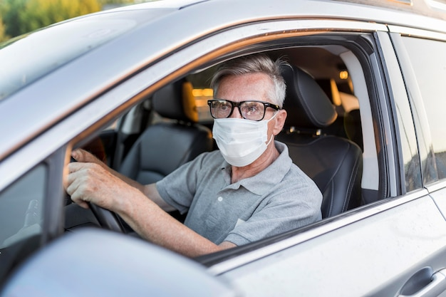 Hombre de tiro medio con máscara conduciendo