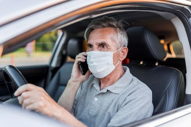 Hombre de tiro medio con máscara médica conduciendo