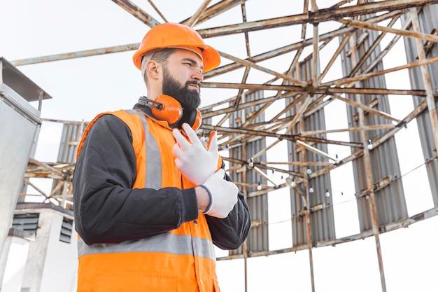 Hombre de tiro medio poniéndose guantes para el trabajo