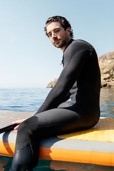 Hombre de tiro medio sentado en la tabla de surf