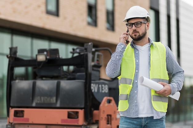Hombre de tiro medio en el sitio de construcción