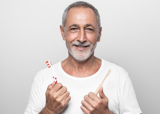 Hombre de tiro medio sosteniendo cepillos de dientes