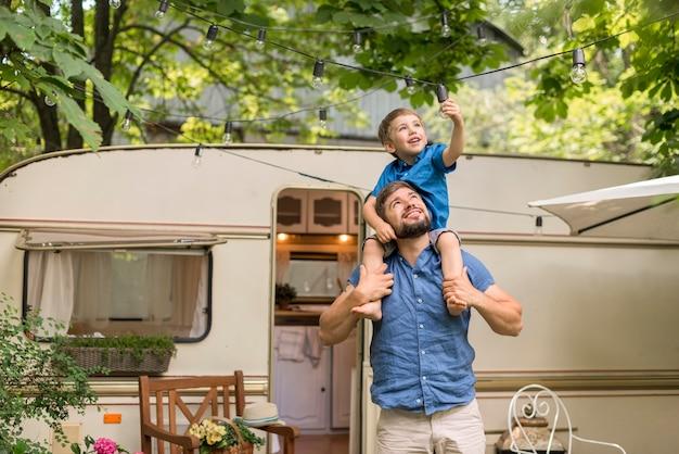 Hombre de tiro medio sosteniendo a su hijo sobre sus hombros junto a una caravana