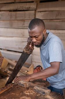 Hombre de tiro medio trabajando con sierra de mano