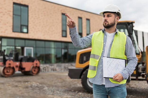Hombre de tiro medio trabajando en el sitio de construcción