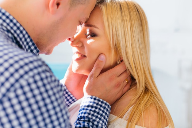 Un hombre toca cara a su bella esposa y quiere besarla