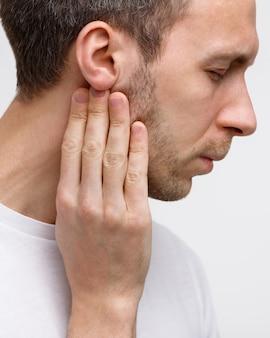 El hombre toca las glándulas linfáticas con los dedos cerca de la oreja.
