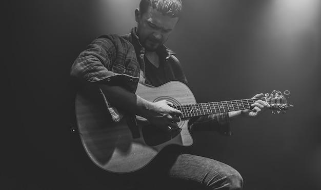 Un hombre toca una guitarra acústica en un concierto parcialmente iluminado.