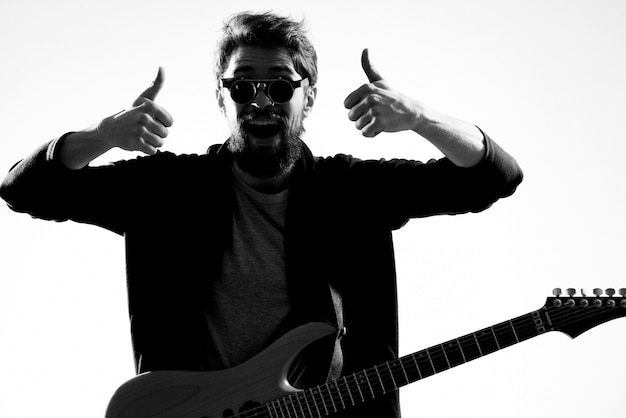 Un hombre toca una guitarra eléctrica, foto en blanco y negro