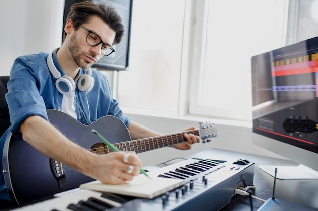 El hombre toca la guitarra y produce una banda sonora electrónica