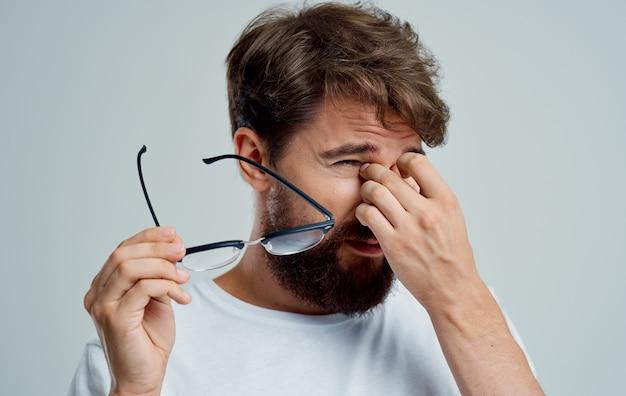 El hombre toca los ojos con las manos y los anteojos problemas de visión.