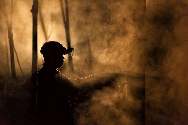 Hombre tocando el árbol de goma en la noche
