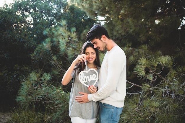 Hombre tocando la barriga de su novia y ella sujeta un corazón con la palabra