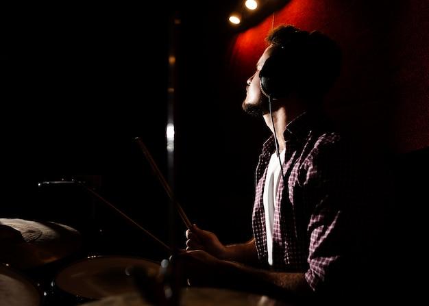 Hombre tocando la batería en la oscuridad