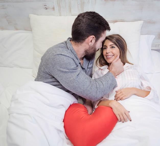 Hombre tocando la cara de la mujer en la cama