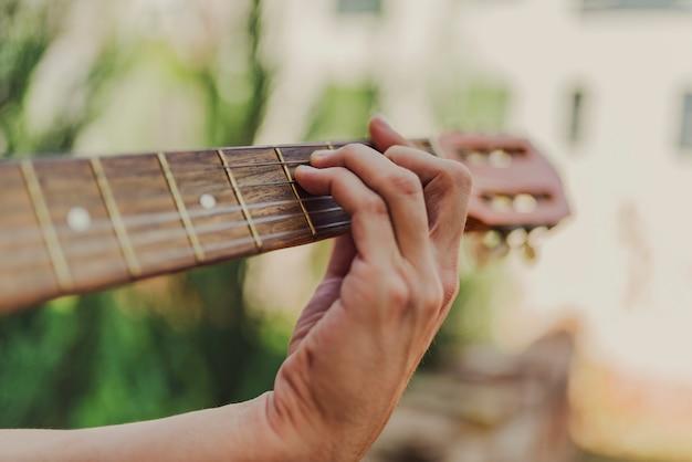 Hombre tocando la guitarra acústica al aire libre